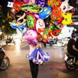 Vietnam - Venditrice di palloncini nelle strade della vecchia Hanoi.